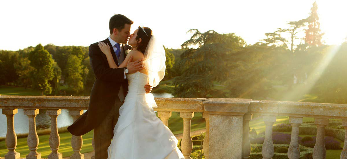 Charlotte and Al embrace as the sun sets on the terrace of Brocket Hall